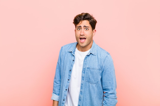 Young handsome man feeling terrified and shocked, with mouth wide open in surprise against pink wall