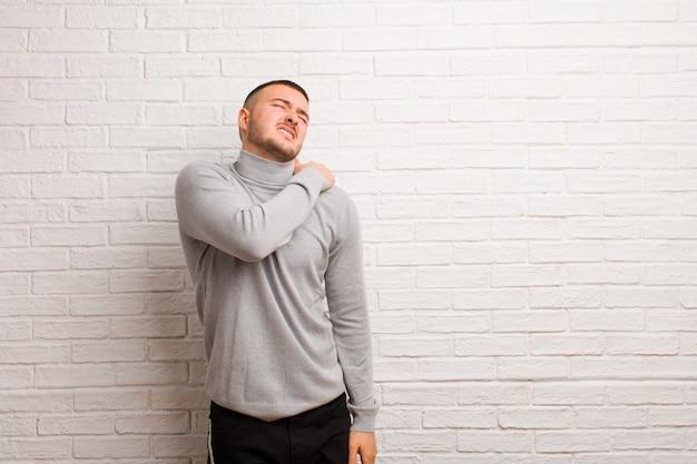 Молодой красивый мужчина, чувствуя усталость, стресс, беспокойство, разочарование и депрессию, страдает от боли в спине или шее у плоской стены