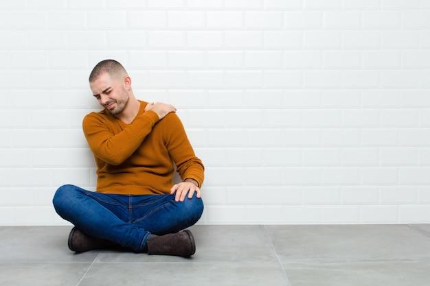 Молодой красивый мужчина, чувствуя усталость, стресс, тревогу, разочарование и депрессию, страдает от боли в спине или шее, сидя на полу