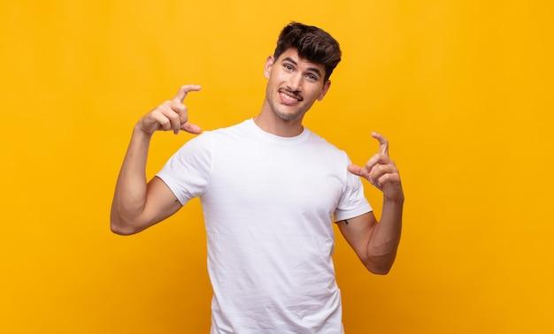 若いハンサムな男は、両手で自分の笑顔をフレーミングまたは概説し、前向きで幸せに見える、ウェルネスの概念