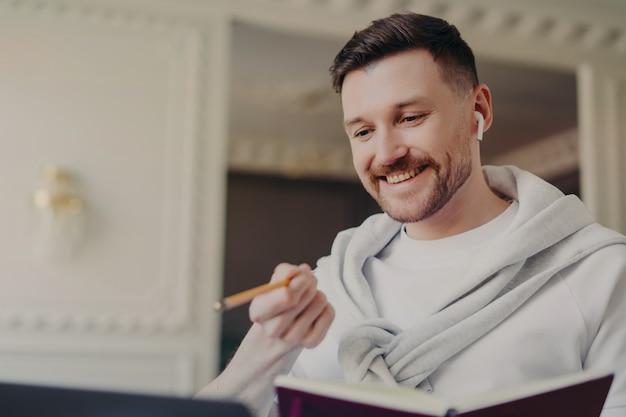 젊은 잘 생긴 남자 프리랜서 또는 사업가, 연필과 책을 들고 노트북 화면을보고 집이나 사무실에서 현대적인 빛의 방에서 작업하는 동안 그의 상사 또는 파트너와 화상 채팅에 이야기