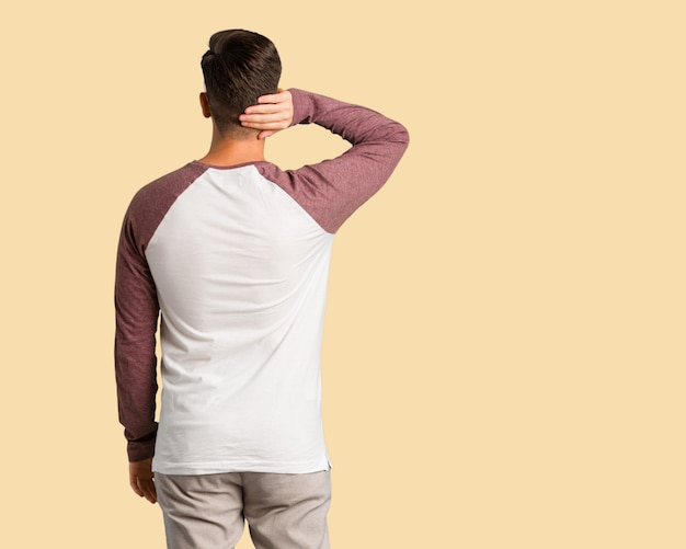 Young handsome man from behind thinking about something