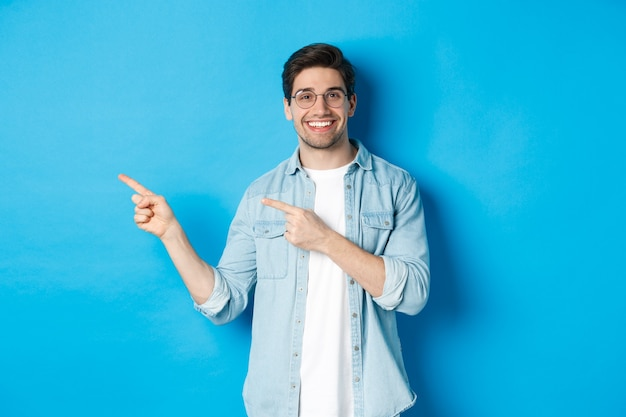 Young handsome man in glasses showing advertisement, smiling and pointing fingers left, making announcement, standing against blue background