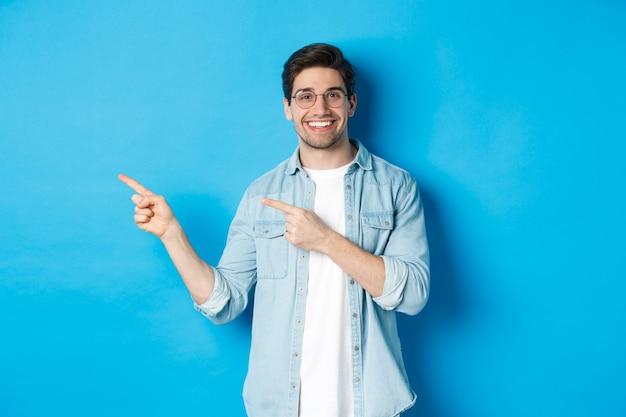 Giovane bell'uomo con gli occhiali che mostra pubblicità, sorride e punta le dita a sinistra, fa un annuncio, in piedi su sfondo blu