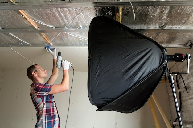 Young handsome man in goggles and work gloves fixing drywall suspended ceiling to metal frame on ceiling insulated with aluminum foil in front of soft box