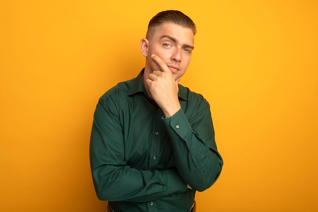 Young handsome man in green shirt lookign at camera with pensive expression on face thinking