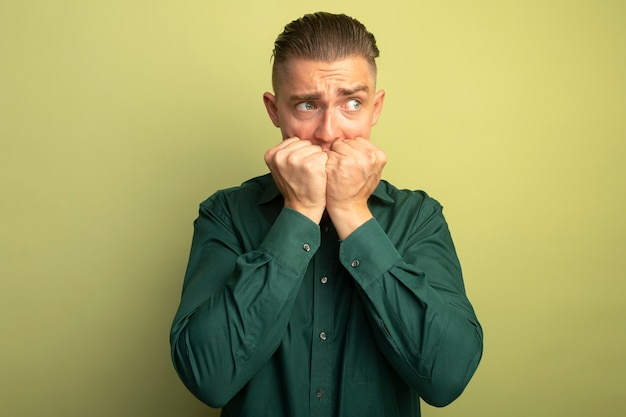 Giovane uomo bello in camicia verde che osserva da parte stressato e nervoso che si morde le unghie in piedi sopra la parete chiara