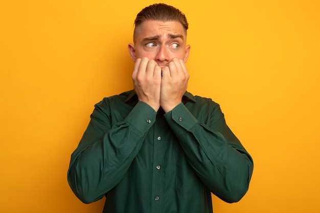 Giovane uomo bello in camicia verde che osserva da parte stressato e nervoso mordendosi le unghie in piedi sopra la parete arancione