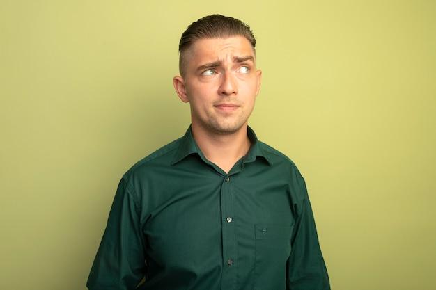 Giovane uomo bello in camicia verde che osserva da parte con espressione scettica