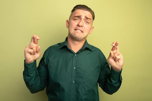 Giovane uomo bello in camicia verde guardando le dita incrociate confuse e preoccupate davanti in piedi sopra la parete chiara