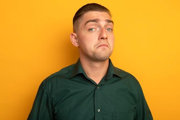 Giovane uomo bello in camicia verde che sorride con l'espressione scettica