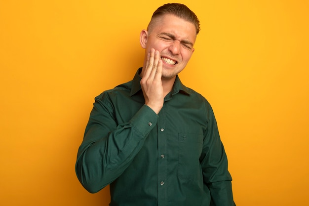 Giovane uomo bello in camicia verde che tocca la sua guancia che ha mal di denti