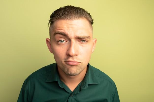 Giovane uomo bello in camicia verde con un sorriso scettico
