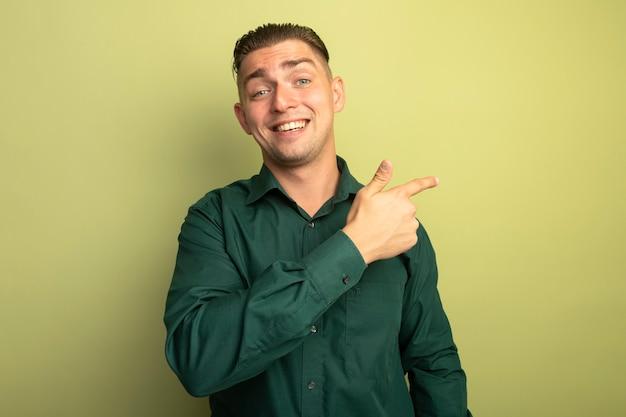 Giovane uomo bello in camicia verde con il sorriso sul viso rivolto con il dito indice di lato