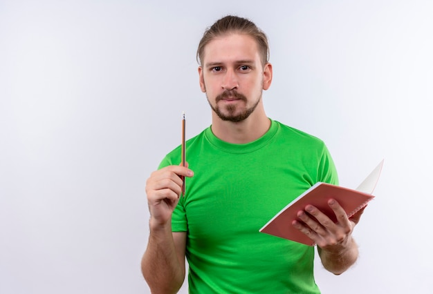 Young handsome man in green t-shirt holding notebook pointing with pencil up haveing a great idea standing over white background