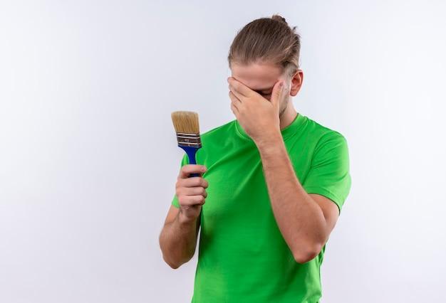 Giovane uomo bello in t-shirt verde che tiene il pennello che copre il viso con la mano in piedi su sfondo bianco