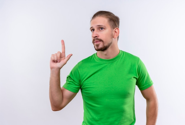 Young handsome man in green t-shirt looking aside pointing finger up looking confident having an idea standing over white background