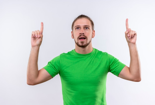 Young handsome man in green t-shirt pointing fingers up looking confident having great idea standing over white background