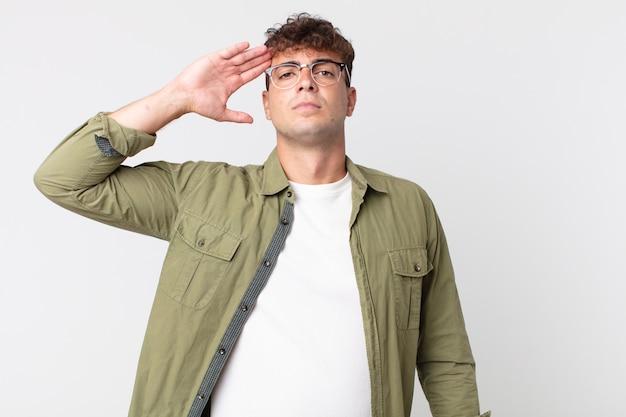 존경을 표시하는 명예와 애국심의 행위에서 군사 경례와 함께 카메라를 인사하는 젊은 잘 생긴 남자