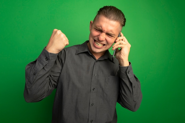 Giovane uomo bello in camicia grigia che stringe il pugno felice ed eccitato mentre parla al telefono cellulare in piedi sopra la parete verde