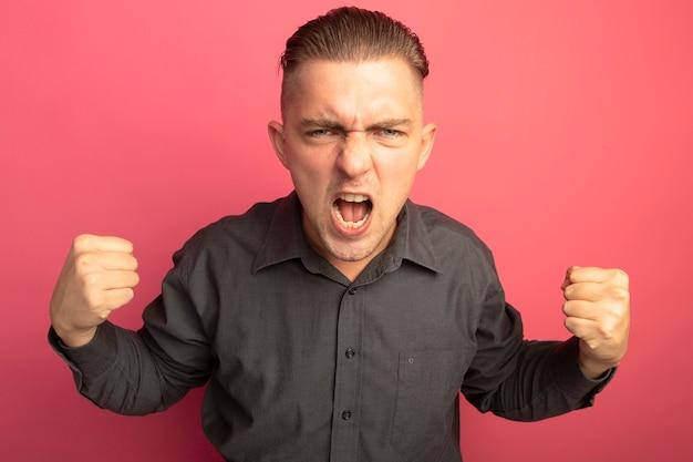 Giovane uomo bello in camicia grigia che stringe i pugni che grida in piedi pazzo pazzo e arrabbiato sopra il muro rosa