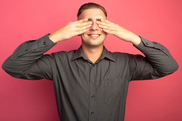 Giovane uomo bello in camicia grigia che copre gli occhi con le mani sorridenti allegramente in piedi sopra il muro rosa