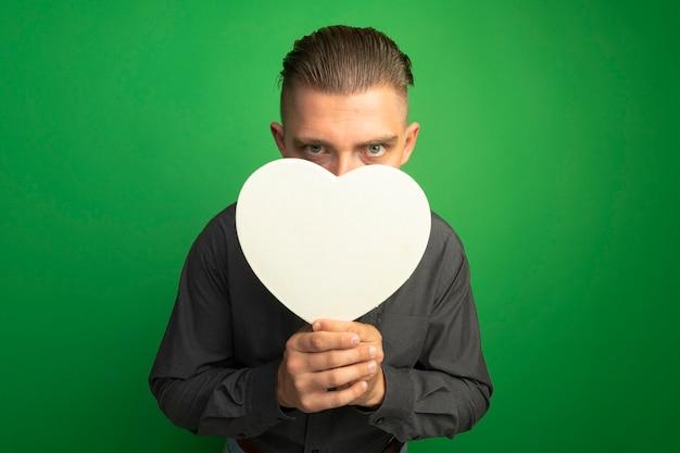 Giovane uomo bello in camicia grigia che tiene cuore di cartone davanti al suo viso che dà una occhiata sopra in piedi sopra il muro verde