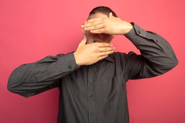 Giovane uomo bello in camicia grigia che tengono le mani davanti al suo viso in piedi sopra il muro rosa