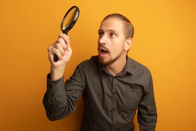 Giovane uomo bello in camicia grigia che tiene la lente d'ingrandimento guardandolo incuriosito