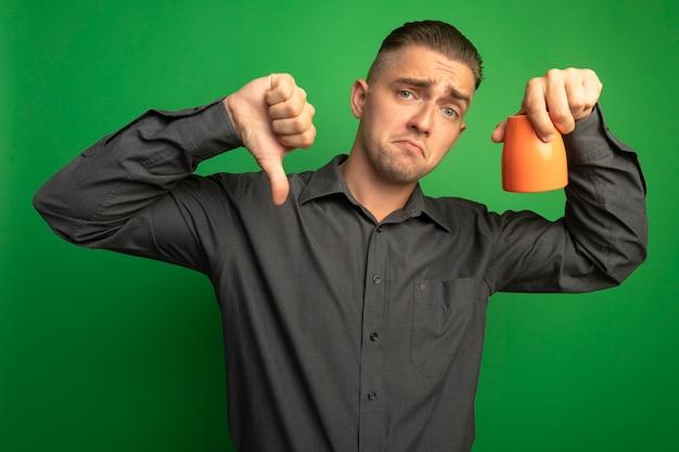 Giovane uomo bello in camicia grigia che tiene tazza arancione guardando la parte anteriore dispiaciuto che mostra i pollici verso il basso in piedi sopra la parete verde