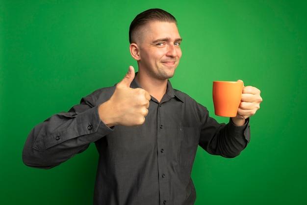 Giovane uomo bello in camicia grigia che tiene tazza arancione guardando davanti sorridendo allegramente mostrando i pollici in su in piedi sopra la parete verde