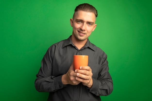 Giovane uomo bello in camicia grigia che tiene tazza arancione guardando davanti sorridente fiducioso in piedi sopra la parete verde