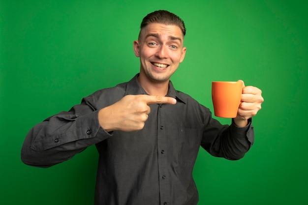 Giovane uomo bello in camicia grigia che tiene tazza arancione che punta con il dito indice sorridendo allegramente in piedi sopra la parete verde