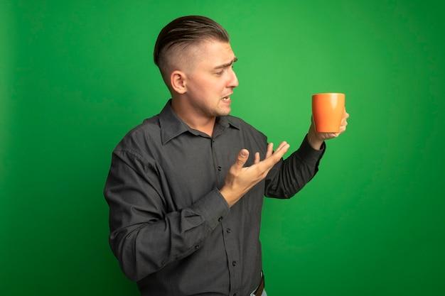 Giovane uomo bello in camicia grigia che tiene tazza arancione presentandolo con il braccio che è confuso