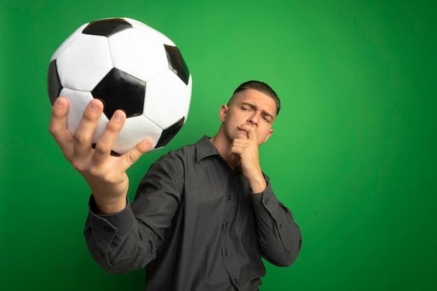 Giovane uomo bello in camicia grigia che tiene pallone da calcio guardandolo incuriosito