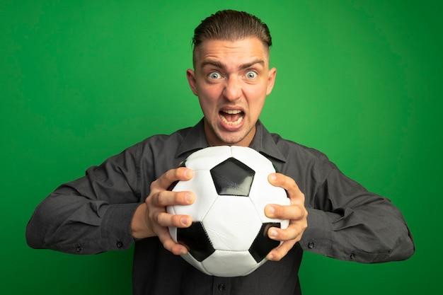 Giovane uomo bello in camicia grigia che tiene pallone da calcio gridando con espressione aggressiva