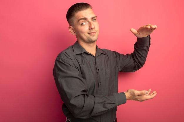 Giovane uomo bello in camicia grigia guardando davanti sorridente fiducioso che mostra il gesto di dimensione con le mani misura il simbolo in piedi sopra il muro rosa