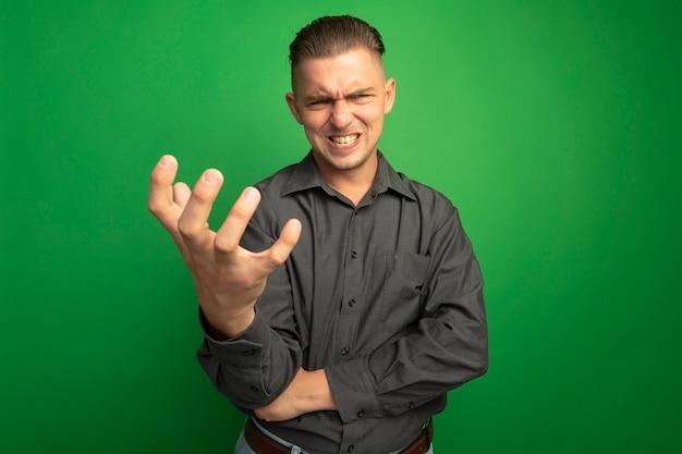 Giovane uomo bello in camicia grigia guardando la parte anteriore con il braccio fuori pazzo pazzo andando selvaggio in piedi sopra la parete verde