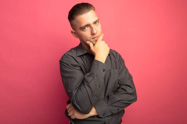 Young handsome man in grey shirt looking at front with hand on his chin thinking standing over pink wall
