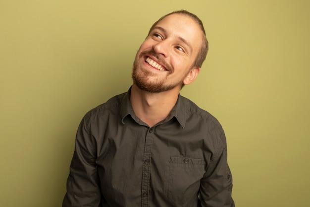 Giovane uomo bello in camicia grigia che osserva in su pensare positivo sorridente ampiamente