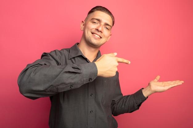 Giovane uomo bello in camicia grigia che presenta qualcosa con il braccio delle sue mani che punta con il dito indice al lato sorridente fiducioso in piedi sopra il muro rosa