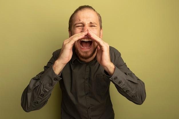 Giovane uomo bello in camicia grigia che grida o chiama qualcuno con le mani vicino alla bocca con espressione infastidita