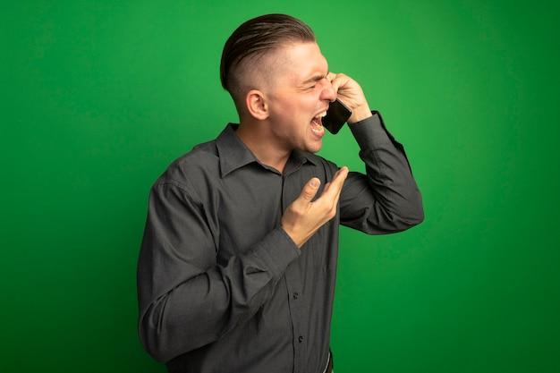 Giovane uomo bello in camicia grigia che grida con espressione aggressiva parlando al telefono cellulare in piedi sopra la parete verde