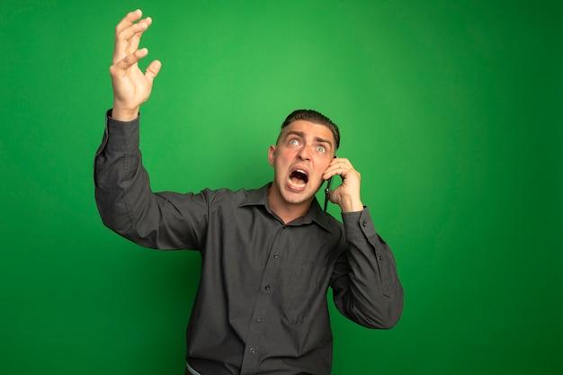 Giovane uomo bello in camicia grigia che grida con espressione arrabbiata con la mano alzata mentre parla al telefono cellulare in piedi sopra la parete verde