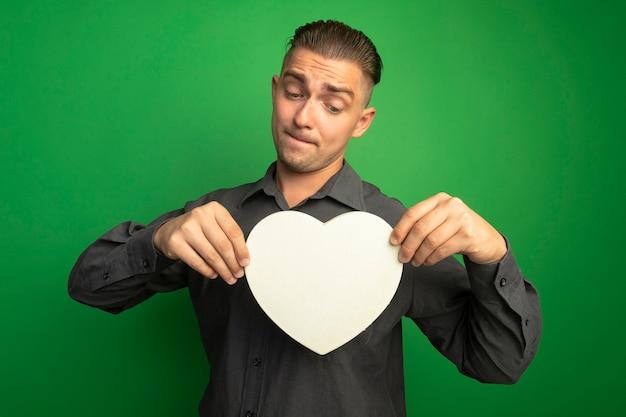 Giovane uomo bello in camicia grigia che mostra cuore di cartone guardandolo con espressione confusa in piedi sopra la parete verde