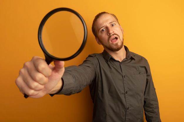Giovane uomo bello in camicia grigia che mostra la lente d'ingrandimento confuso