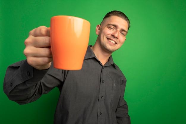 Giovane uomo bello in camicia grigia che mostra tazza arancione sorridente con la faccia felice in piedi sopra la parete verde