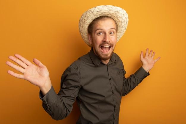 Giovane uomo bello in camicia grigia e cappello estivo braccia aperte ai lati felici ed eccitati