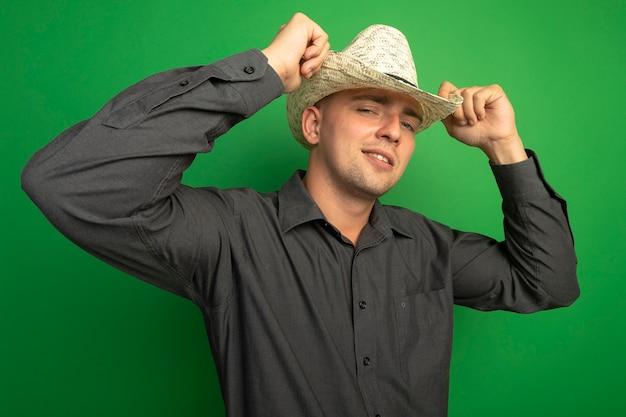 Giovane uomo bello in camicia grigia e cappello estivo guardando davanti con espressione fiduciosa in piedi sopra la parete verde