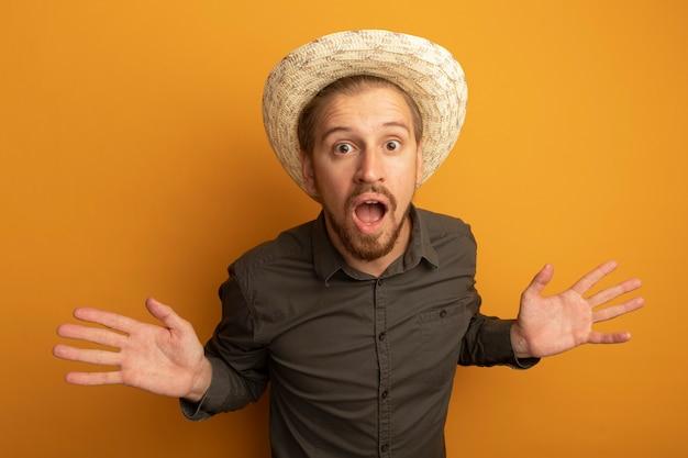 Giovane uomo bello in camicia grigia e cappello estivo sorpreso e stupito a braccia aperte